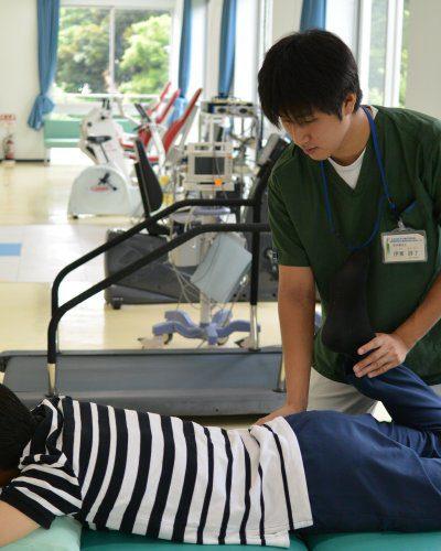 ベッドの上の患者さんの脚に手を添えている伊東さん