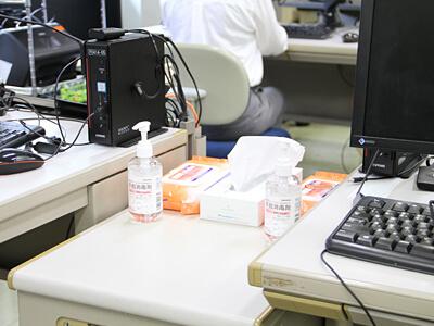 机の間に設置されたスペーサーと消毒用品