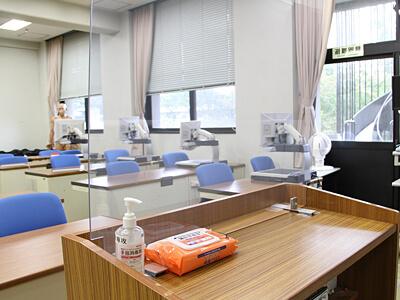 教卓上に設置した飛沫防止用アクリル板と消毒用品および窓辺に設置されたサーキュレーター