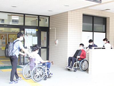 車いすに乗った患者さんをスロープから降ろすために必要な技術について、実際に車いすに乗り介助する側・される側の両方の体験をしながら指導を受ける学生達